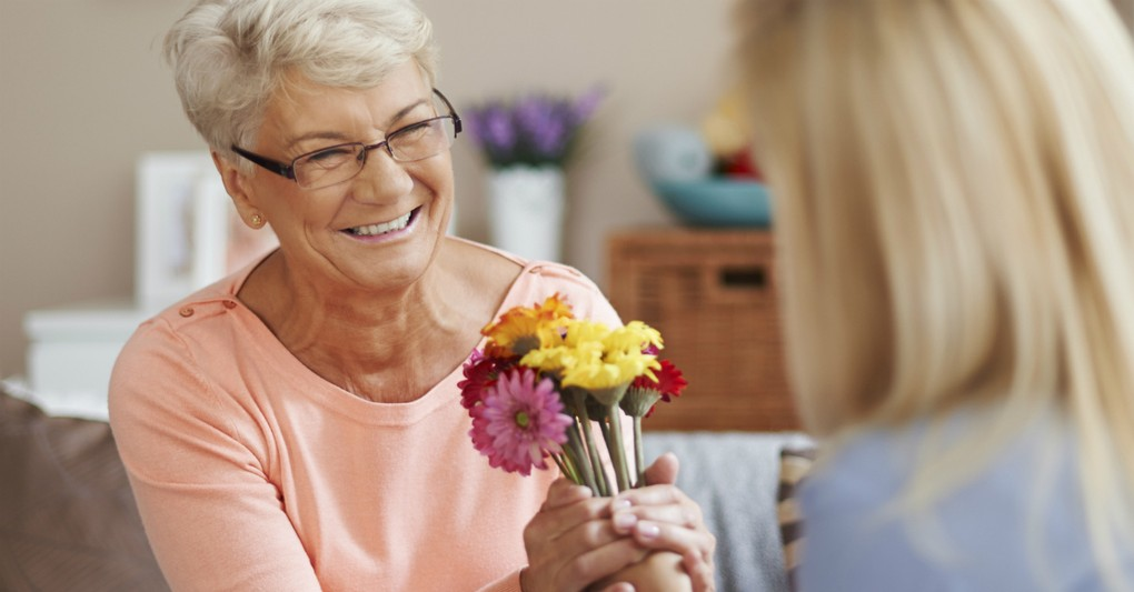 senior woman accepting flowers, ways God tells you how much you matter