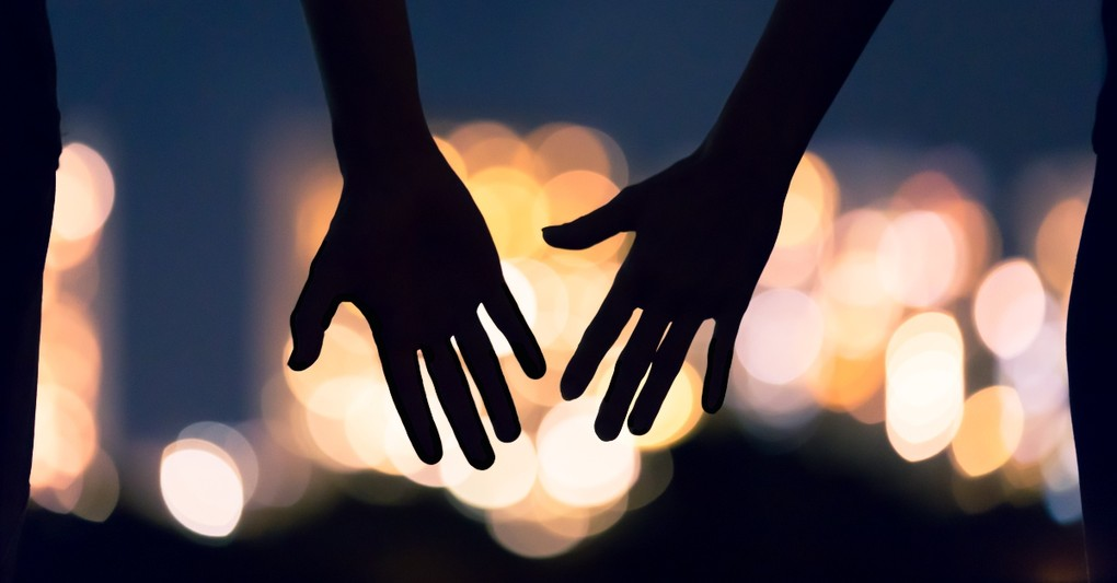 silhouette of hands reaching against city lights backdrop, things to stop taking for granted after pandemic