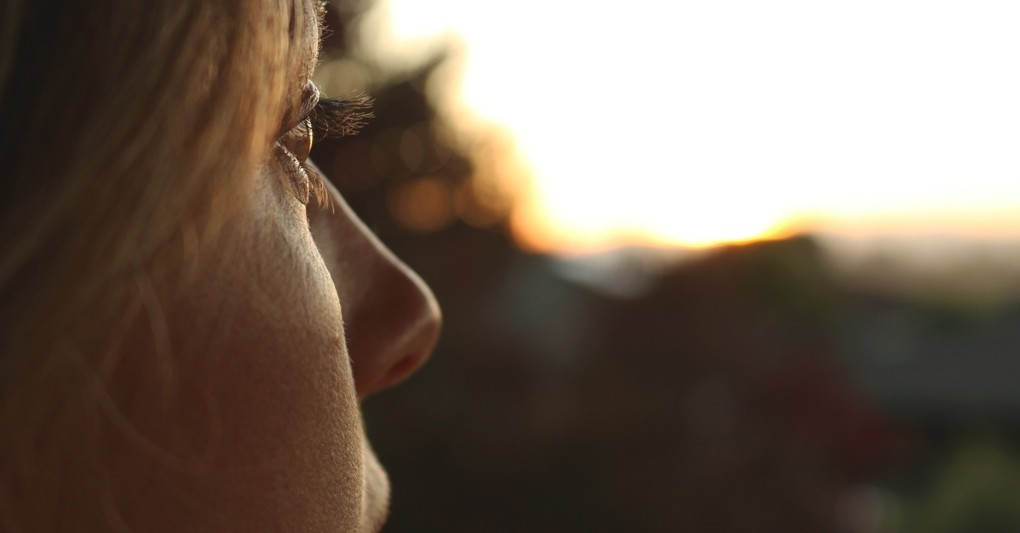 close up of woman gazing off into the middle distance sunset light, discern voice of God