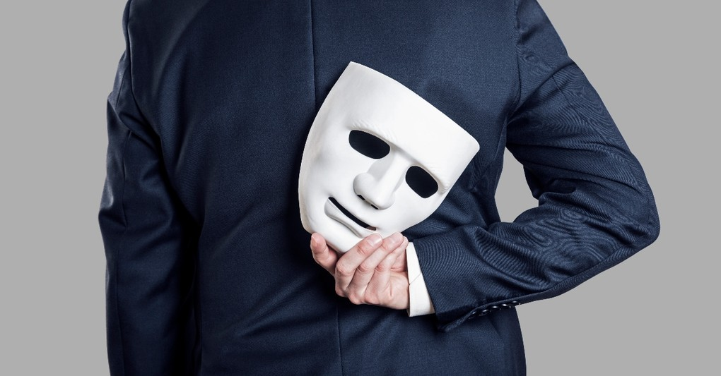 man in suit holding white mask behind his back