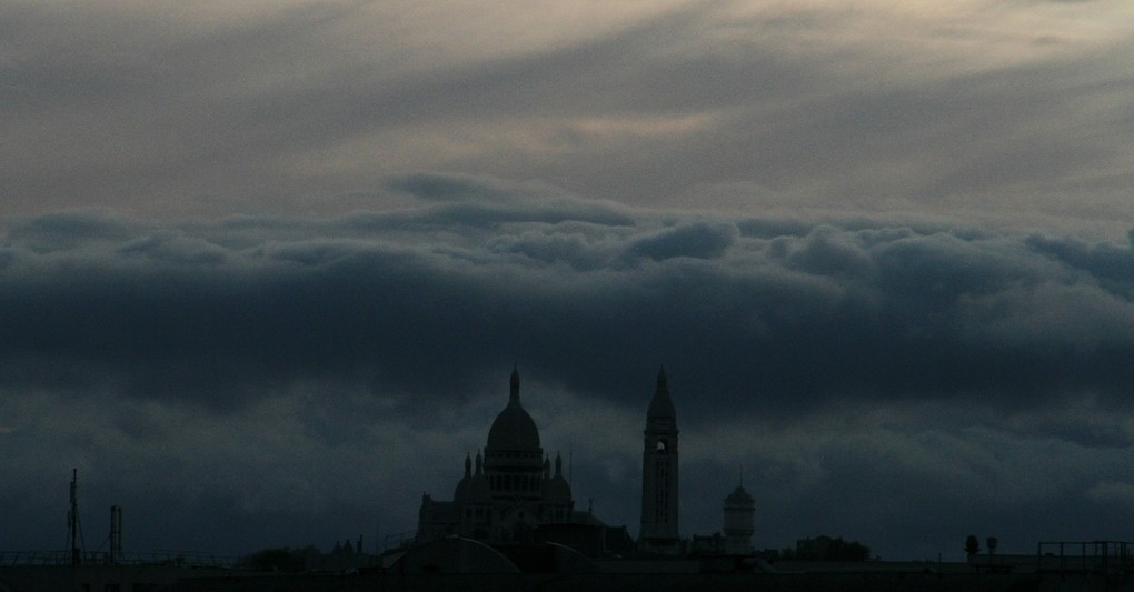 dark skyline with church and bell tower under storm clouds, hymns with messages for christians during times of crisis