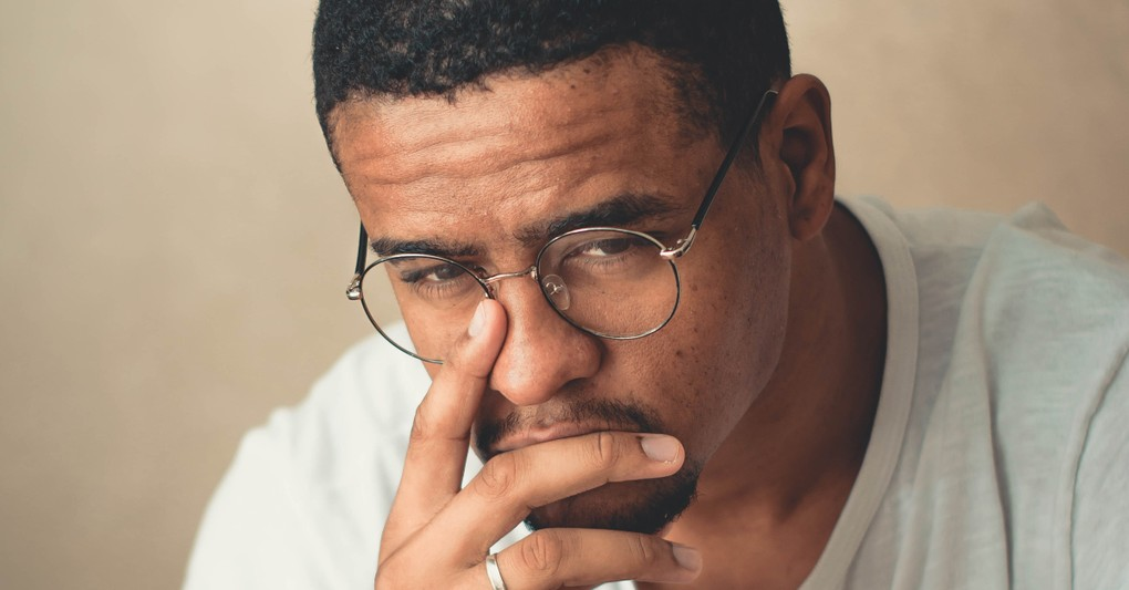 man with hand on chin worried uncertain
