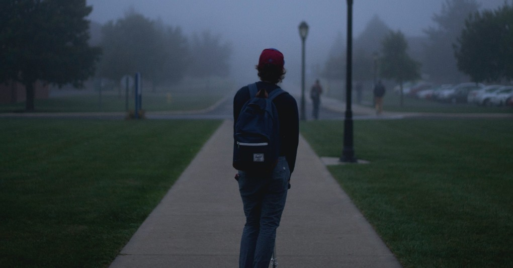 young man with backpack standing in dark fog on college campus, affirmations for parents of prodigal child