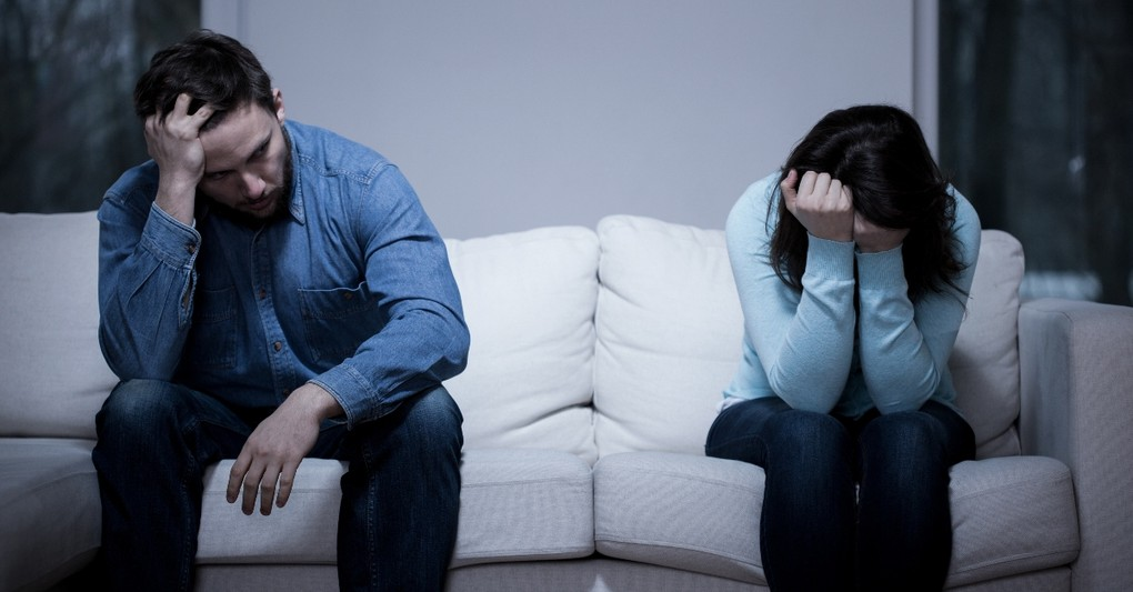 man and woman looking sad and upset sitting on opposite ends of a couch, where is god in a broken marriage