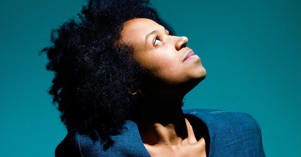 young confident black woman looking up into light