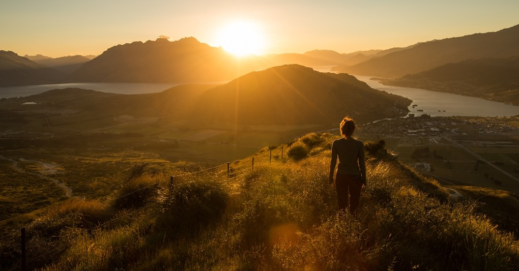 woman standing on hillside overlooking valley as sun rises, how to never miss what God is doing in your life