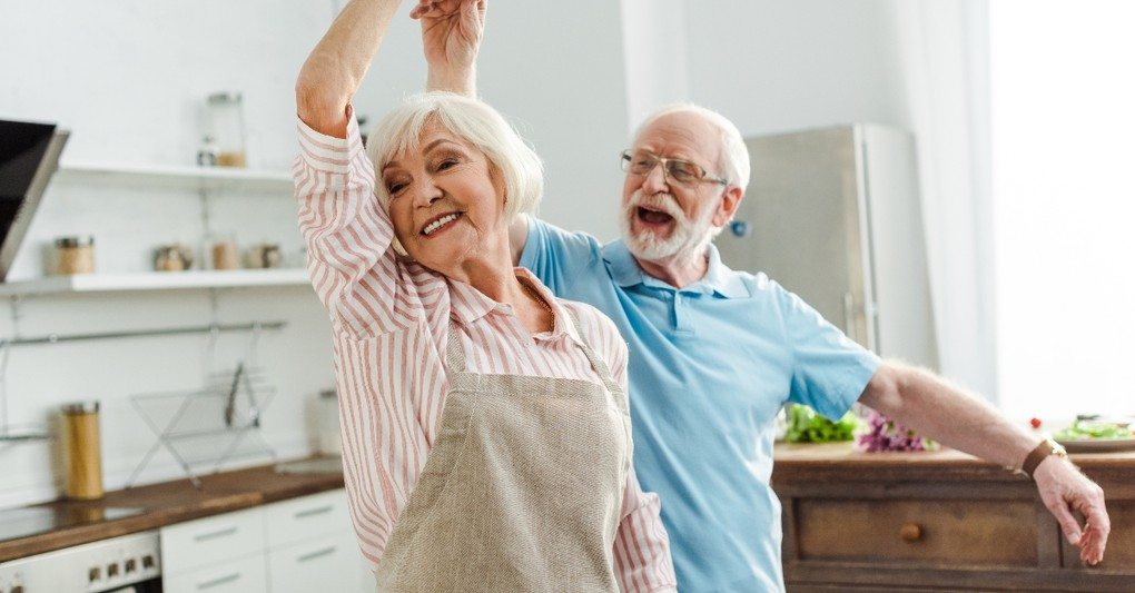 happy senior couple dancing in the kitchen, wonderful time to be alive