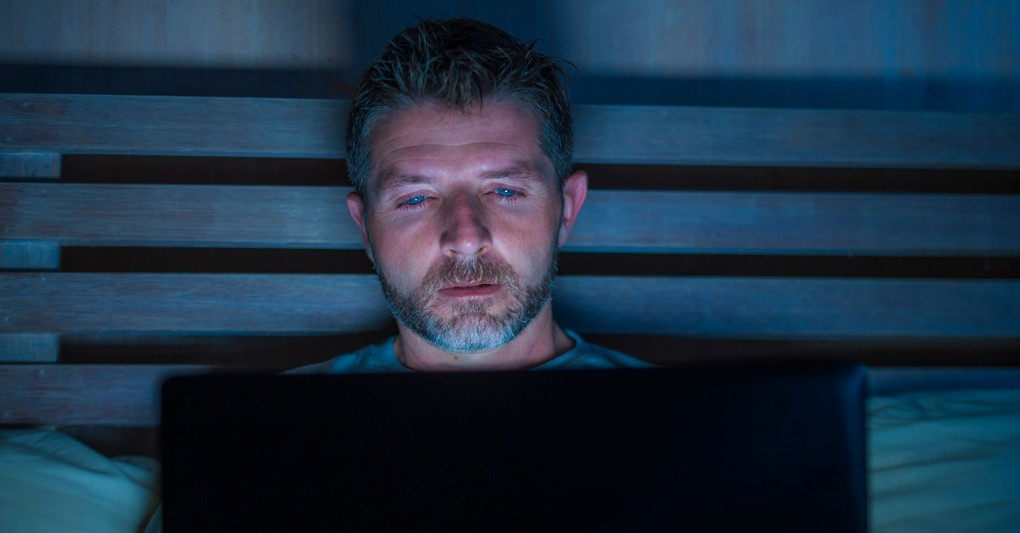 man watching laptop late at night in bed