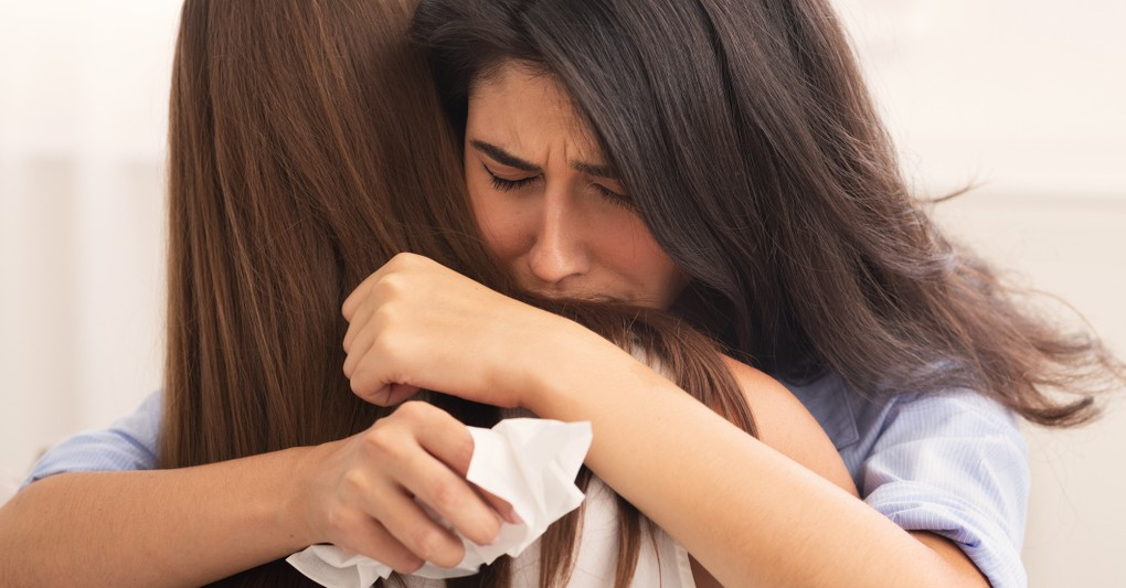 friends hugging while crying
