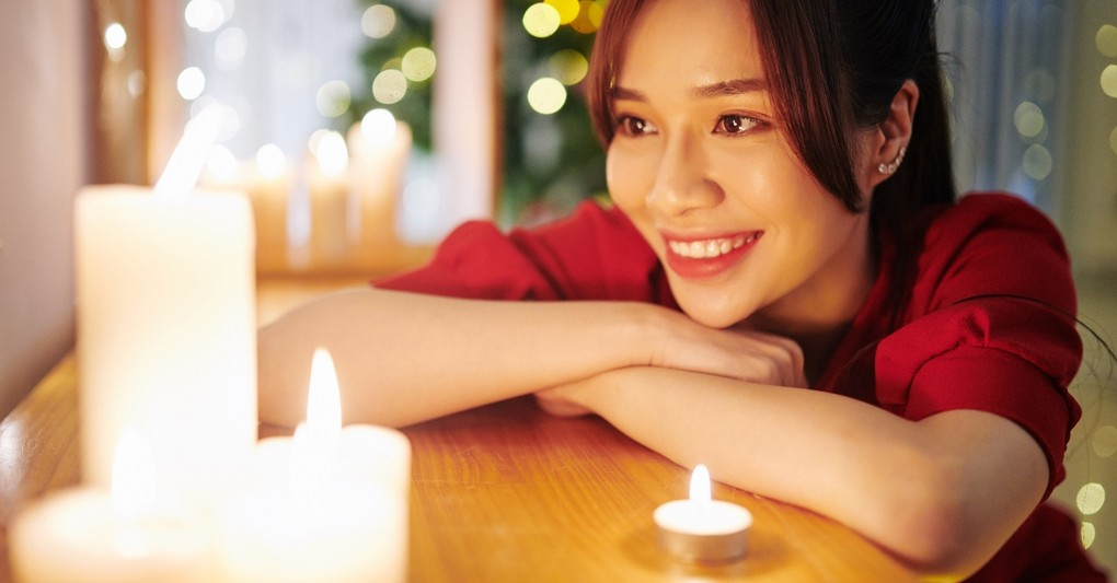 woman smiling at candles at christmas, how to hear god's voice this christmas