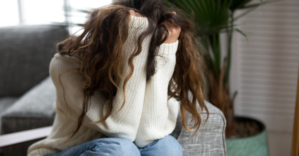 woman hiding in sweater looking afraid and worried, prayers for moments of anxiety