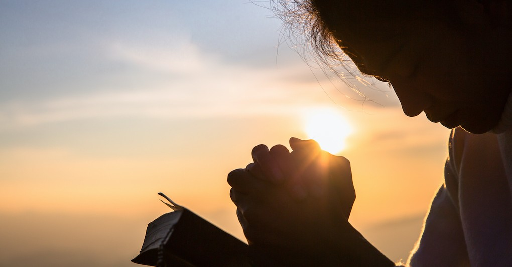 Woman praying over Bible outside at sunrise, good things come to those who wait