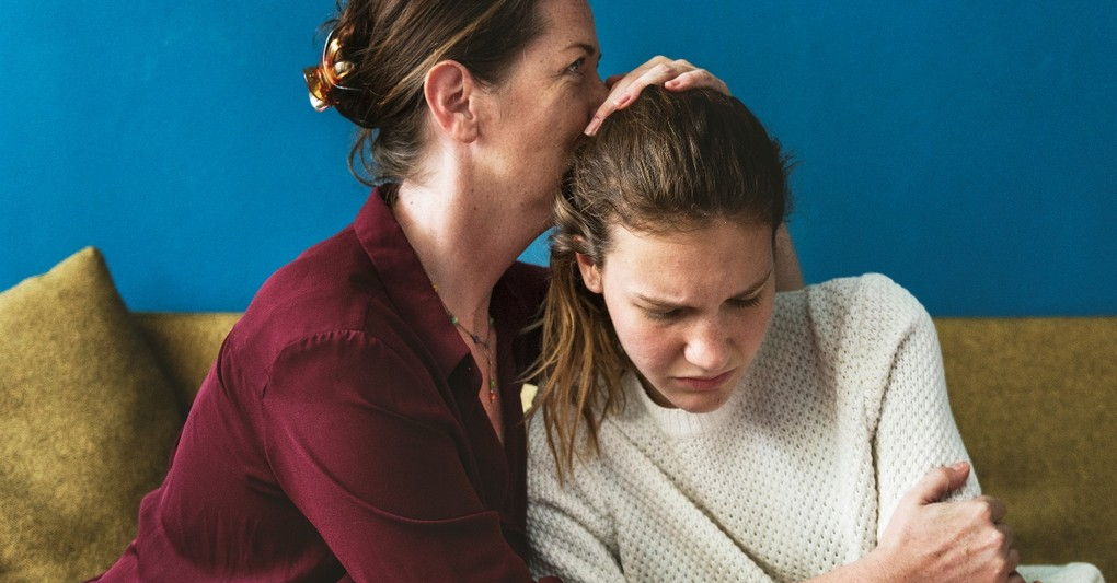 teenage daughter looking distressed and mother hugging her, what to do when you think your daughter struggles with mental health