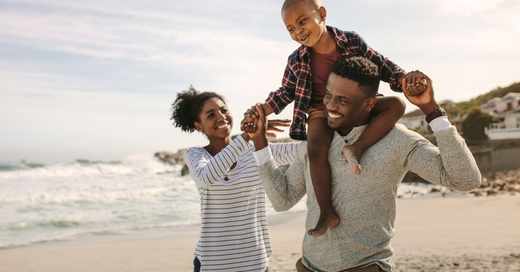 family laughing walking together on beach