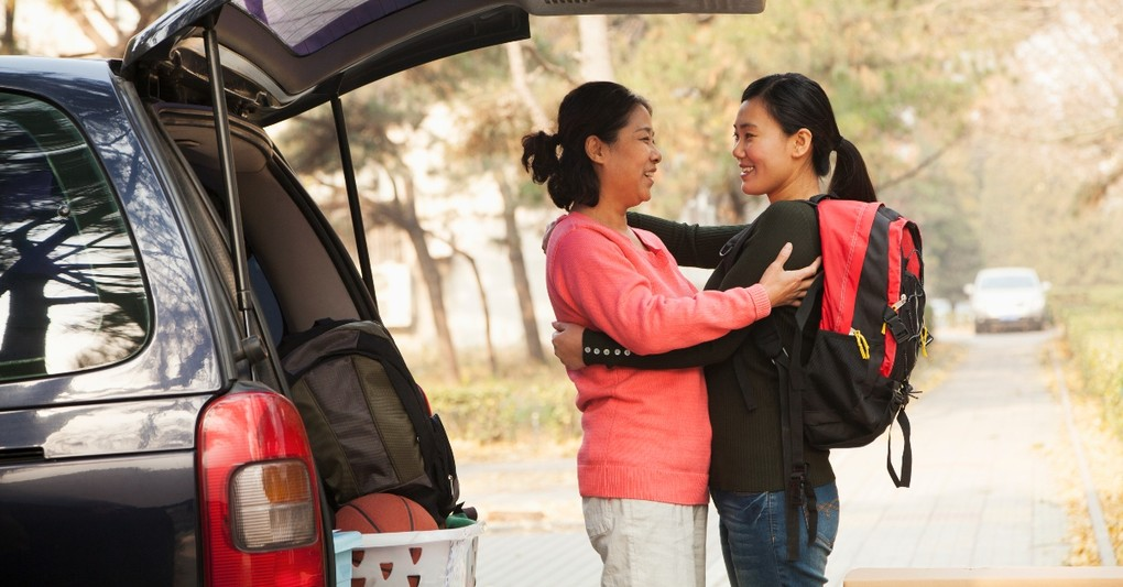 girl moving out of the house saying goodbye to mom at car