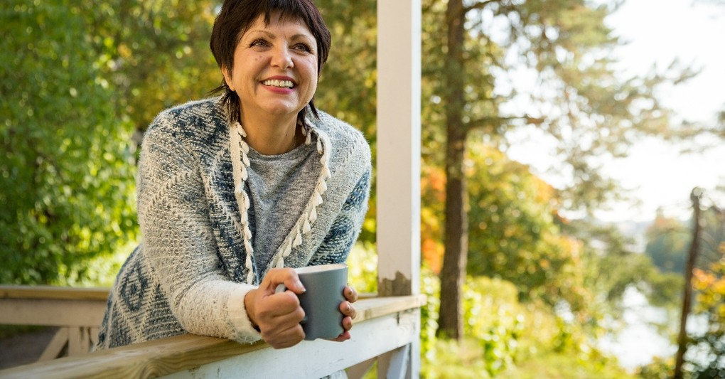 mature woman standing with mug on front porch in autumn looking relaxed and happy, tips for simple stress-free fall
