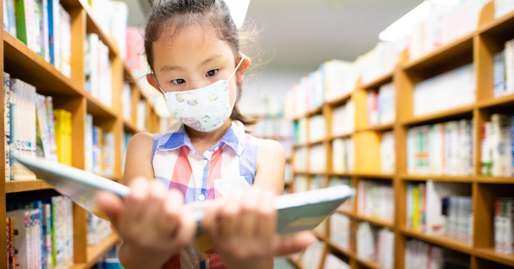 young girl wearing mask reading book in school library, return to school prayers protection