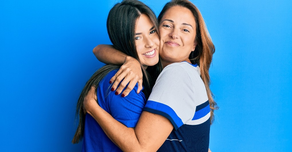 mom and older daughter hugging looking happy