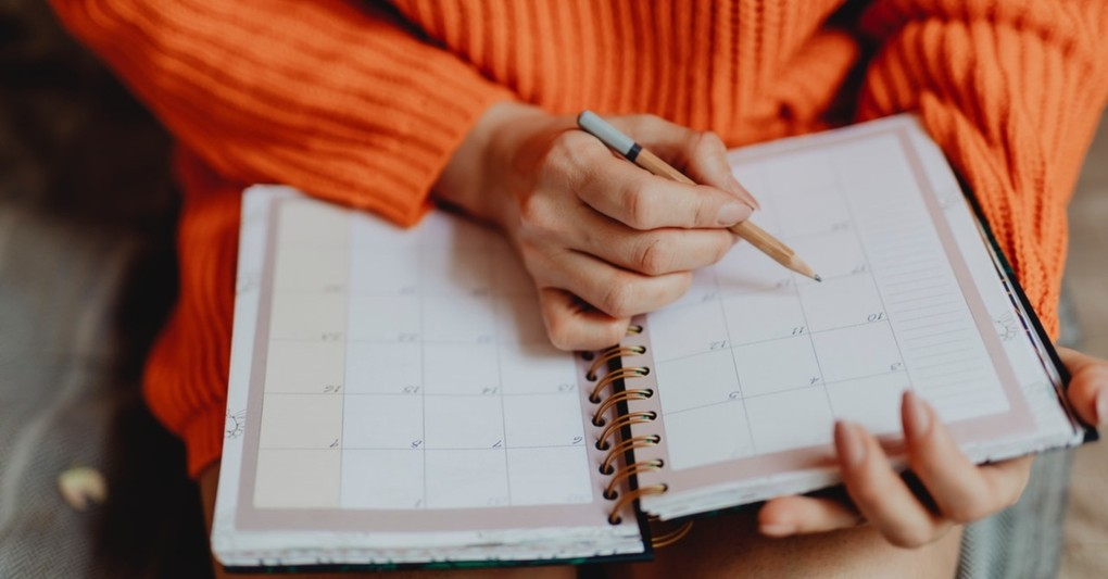 woman writing in calendar planner