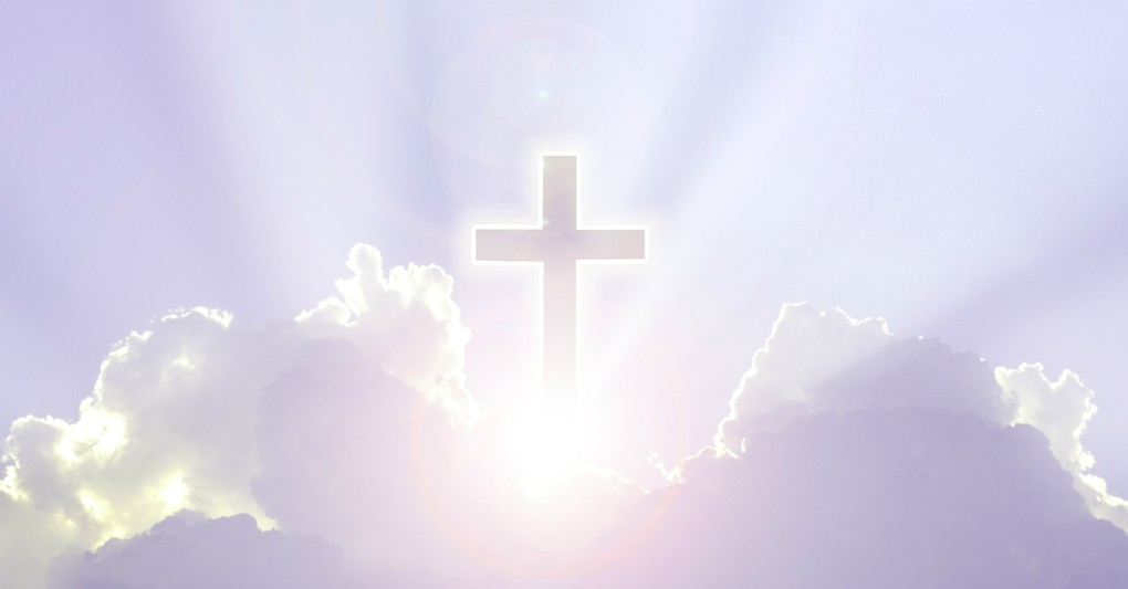 silhouette of cross in the clouds with bright light behind