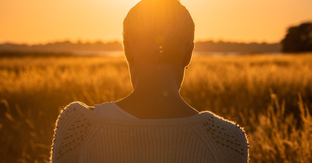 back of woman looking down in field, beautiful things god sees in you