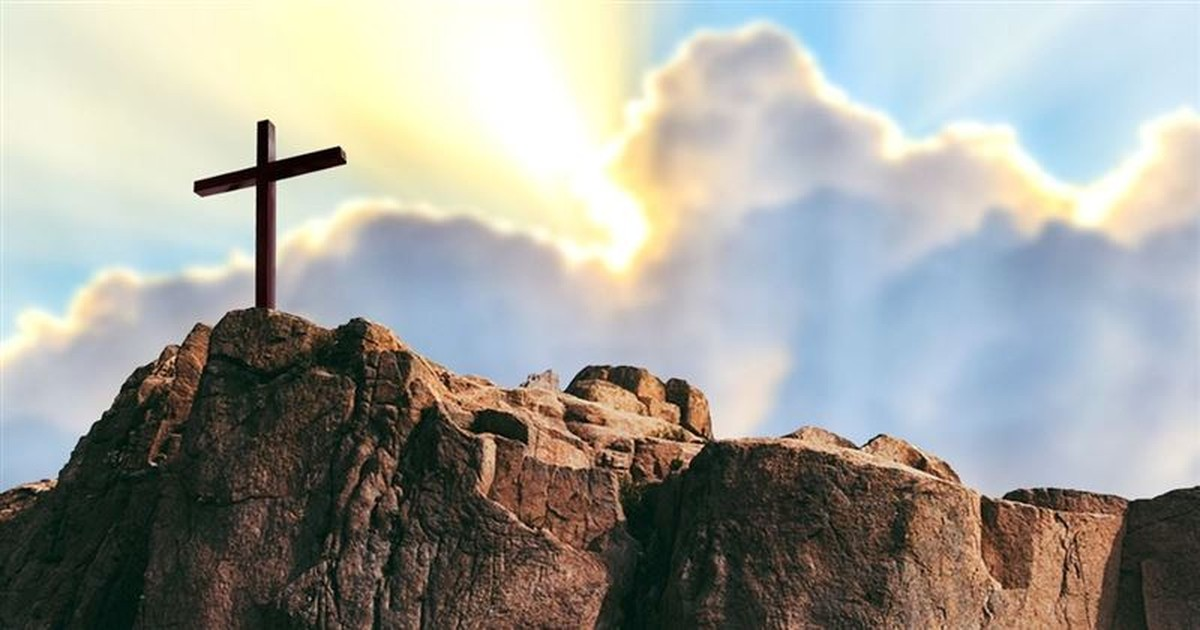 cross on mountain top with sky background