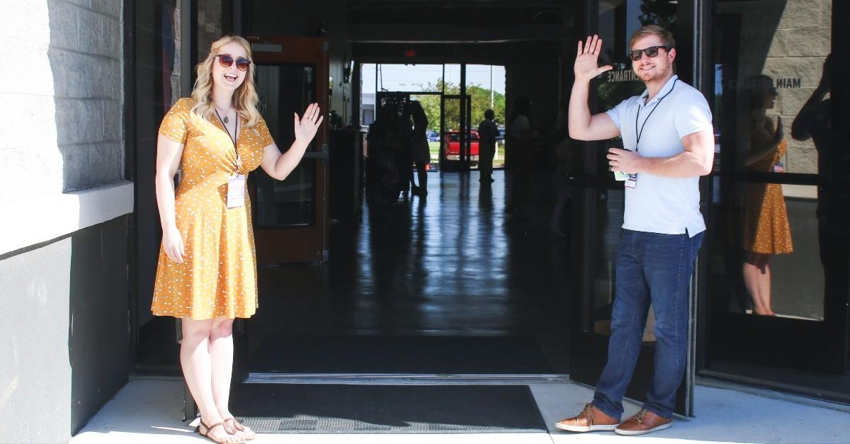 Church greeters waving at the door