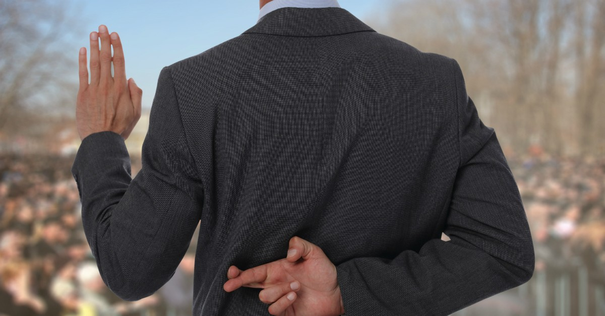 Man with fingers crossed behind his back, lying