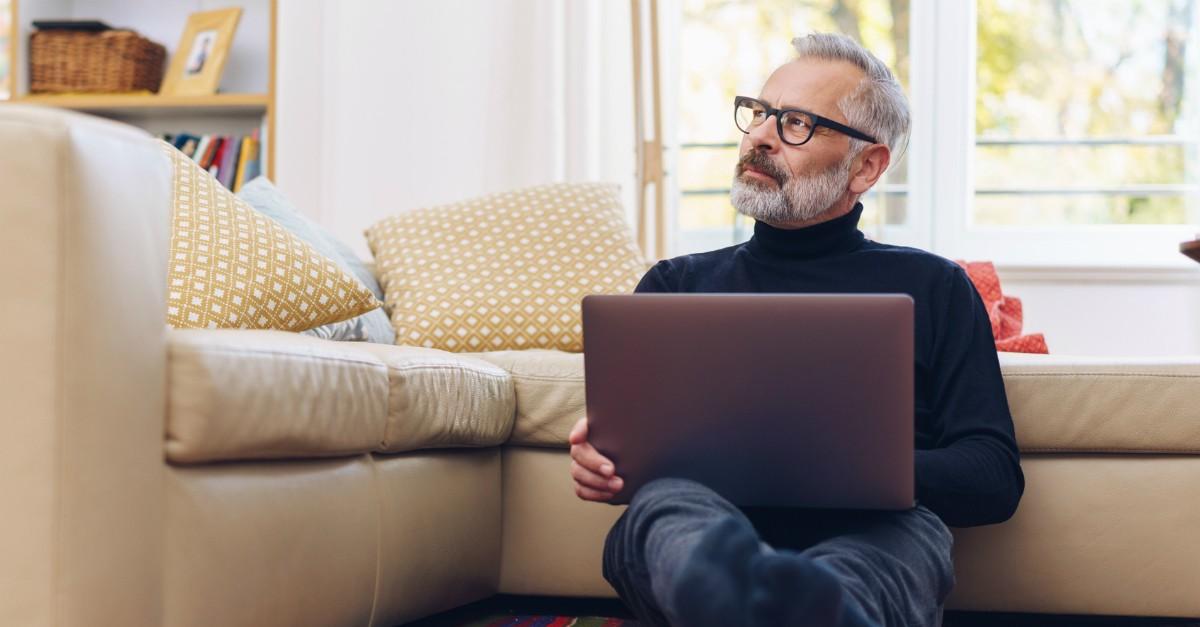Senior man on a laptop thinking