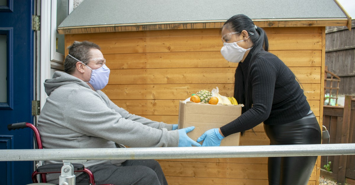 Woman in face mask giving a man a box of groceries