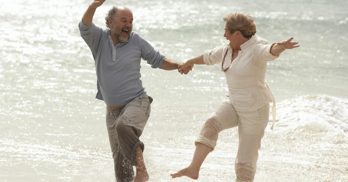 happy senior retired couple splash and laugh at beach
