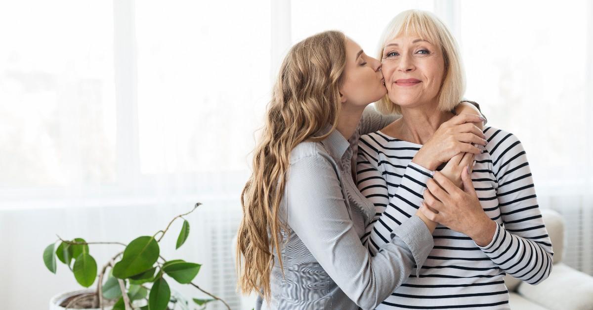 adult child kissing mom on cheek