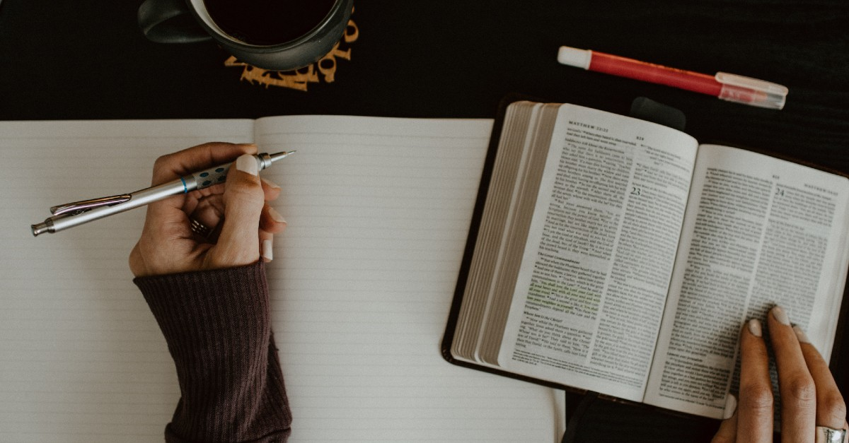woman reading bible and journaling