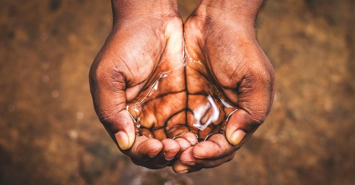 cupped hands holding water, satisfied in god