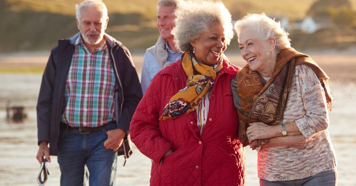 happy multicultural senior friends walking on beach