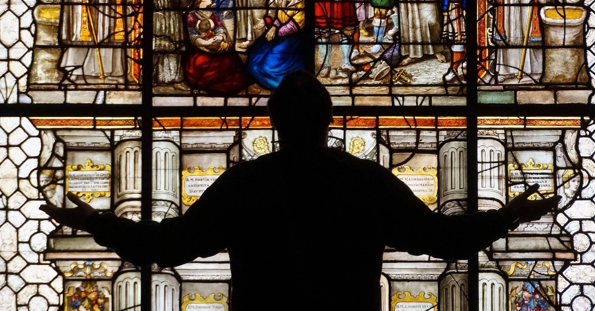 silhouette of man worshipping before a beautiful stained glass window, hymns to silence satan's lies