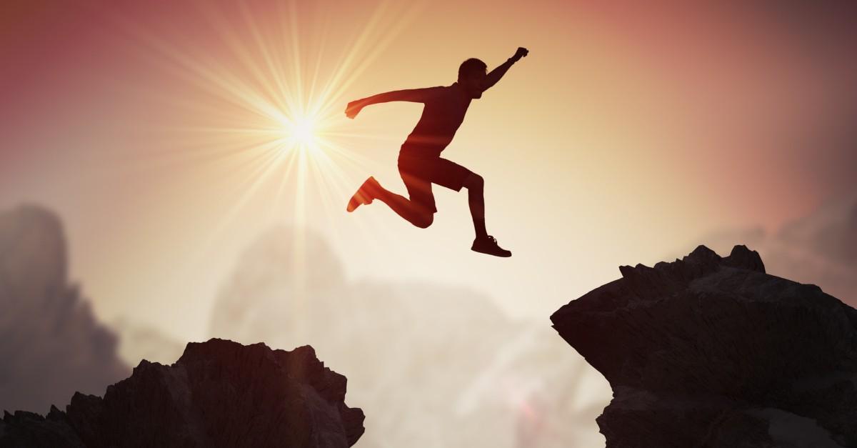 brave courageous man jumping betwen two mountain cliffs at sunset