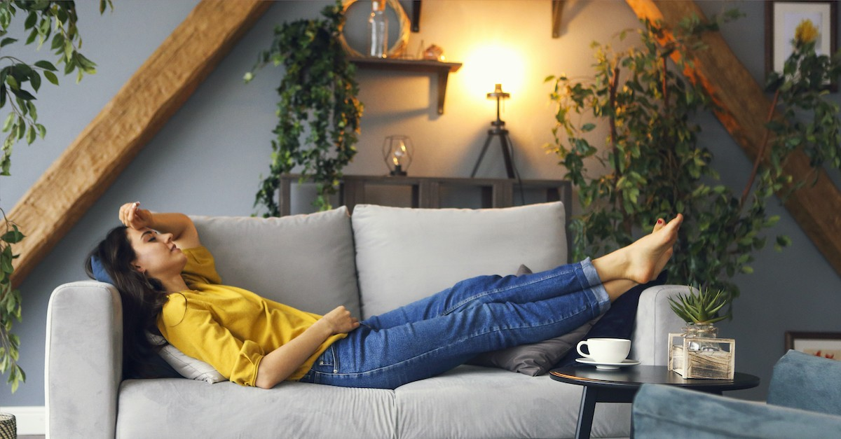 woman resting on sofa with low lighting and plants in background