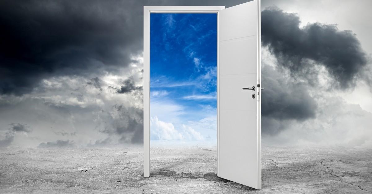 open door revealing blue sky in middle of dark sky to signify opportunity or carpe diem