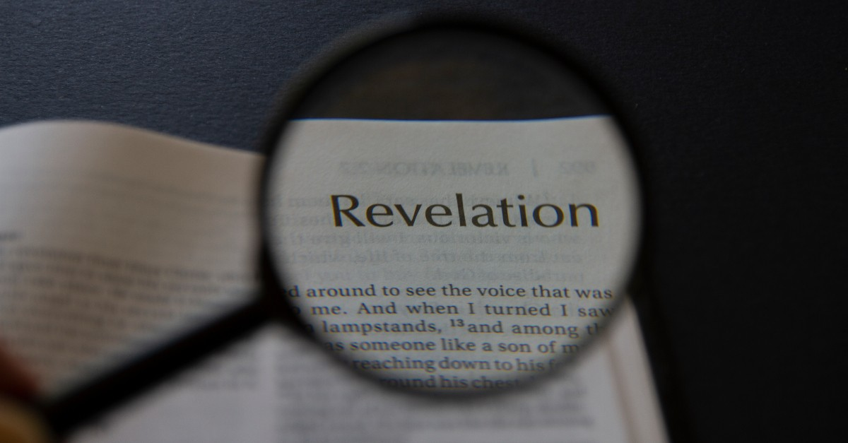 bible open to revelation with magnifying glass