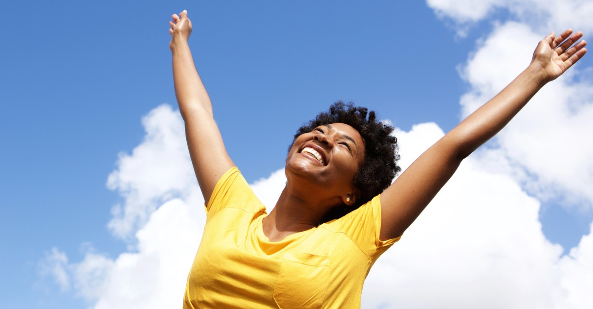 joyful woman with hands raised in praise and free of worry
