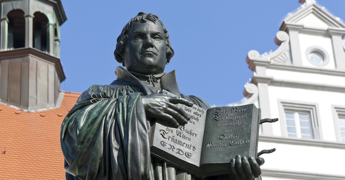 statue of Martin Luther holding book in front of church, Martin Luther and his 95 theses