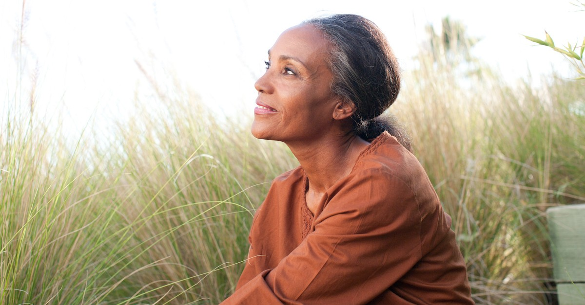 woman sitting in field peacefully looking out into nature, blessed are the peacemakers