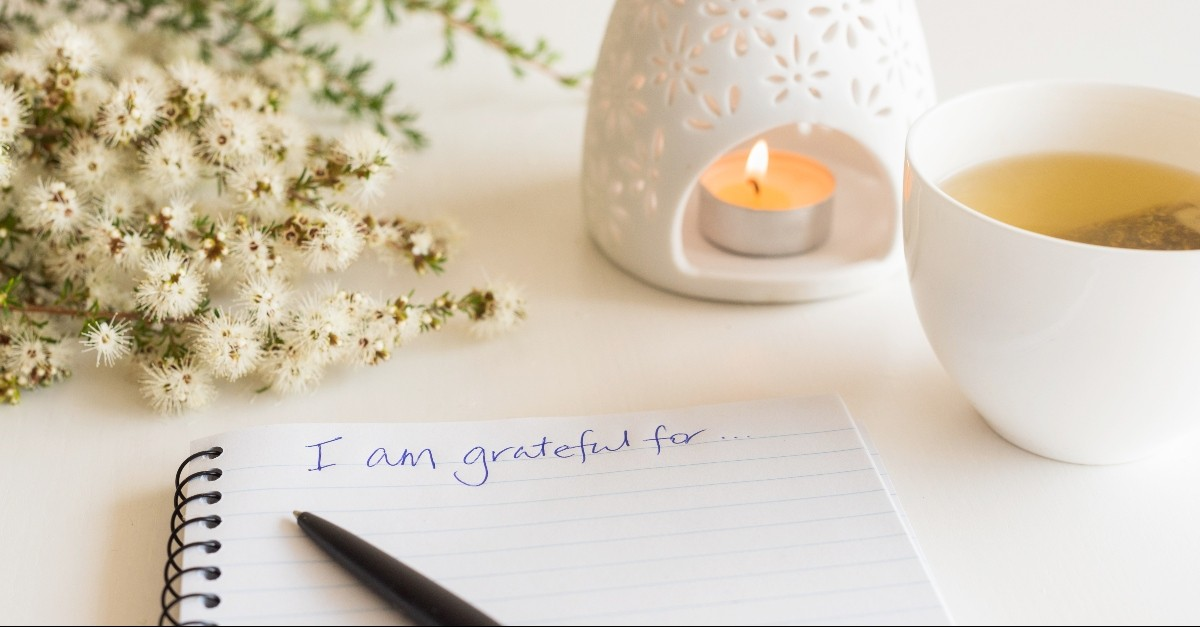 Journal to be grateful today, candle, and tea