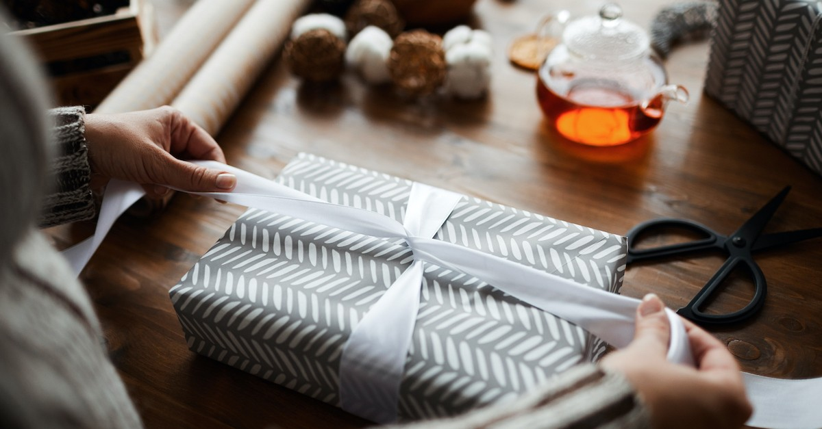 gift being wrapped on table with hot tea in the background