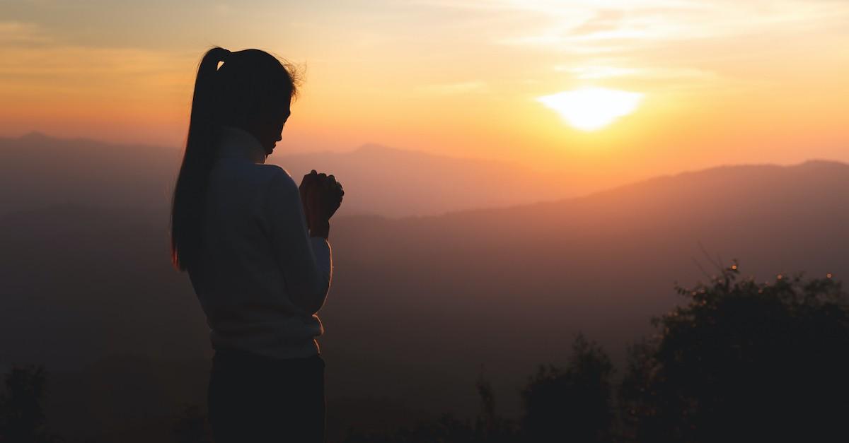 woman praying outside at sunset
