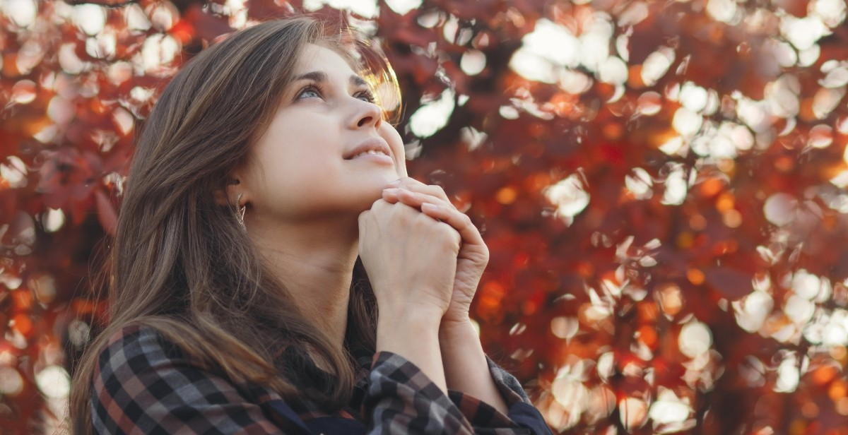 Woman praying near some fall leaves