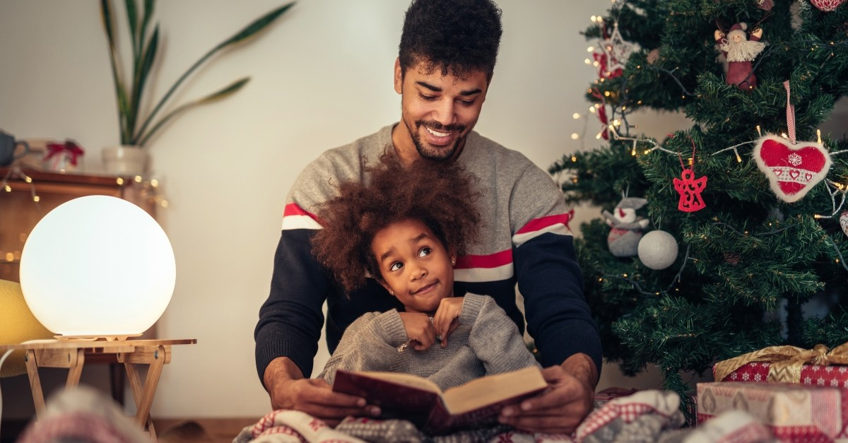 Dad and daughter reading together at Christmas