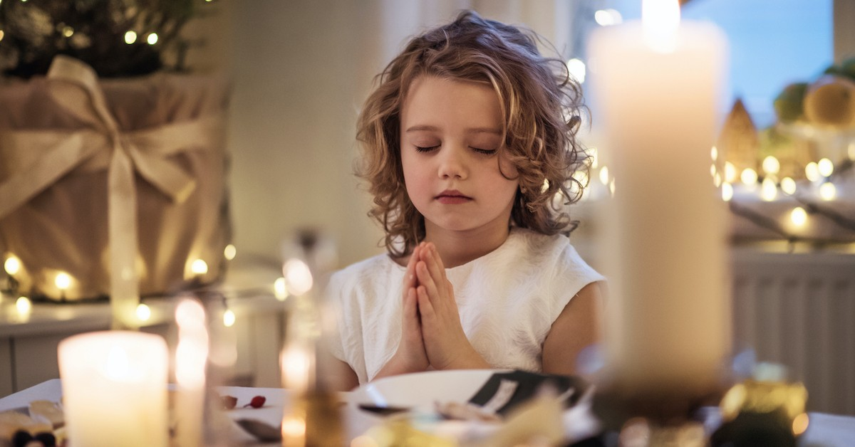 Sweet child praying at Christmas surrounded by candlelight, Inspiring Christmas Eve Prayers