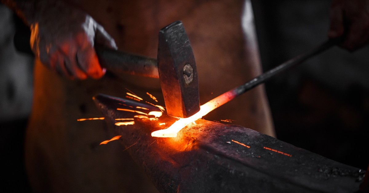 Blacksmith working a piece of metal, refiner's fire